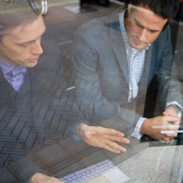 businessmen working remotely through cafe window